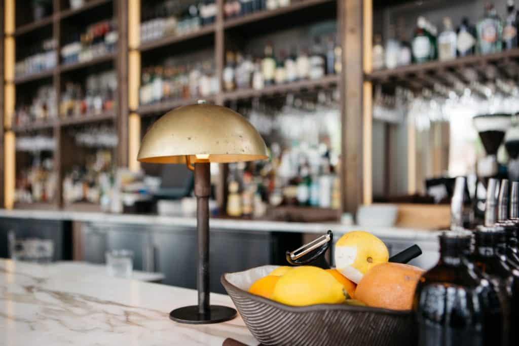 A bar top with a basket of oranges on the counter